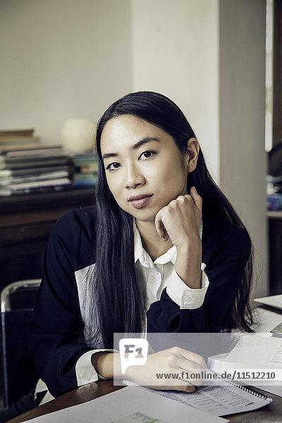 Frau sitzt am Schreibtisch im Büro  Porträt