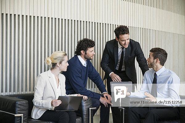 Die Mitglieder des Geschäftsteams arbeiten an einem Projekt mit Hilfe eines digitalen Tabletts zusammen.