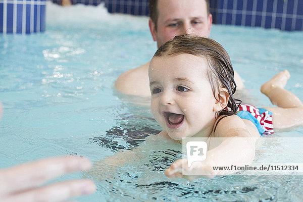 Kleines Mädchen  das mit Hilfe der Eltern schwimmen lernt.