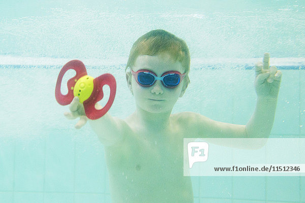 Junge spielt mit Spielzeug unter Wasser