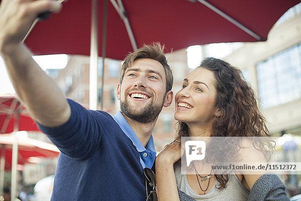 Pärchen posieren für einen Selfie in einem Outdoor-Café