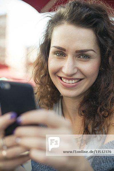 Junge Frau mit Smartphone  lächelnd  Portrait