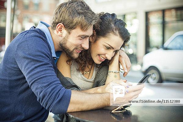 Paar sitzt zusammen im Freien und schaut auf das Smartphone