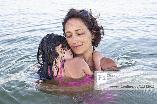 Mutter und Tochter watend im Meer