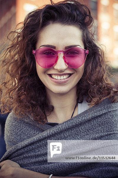 Frau mit rosa Sonnenbrille  fröhlich lächelnd  Portrait