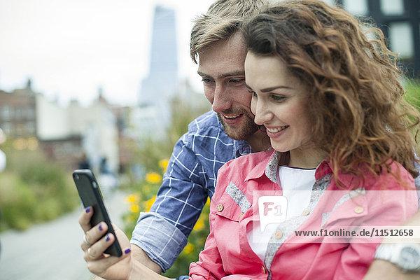 Paar  das sich das Smartphone gemeinsam im Freien anschaut