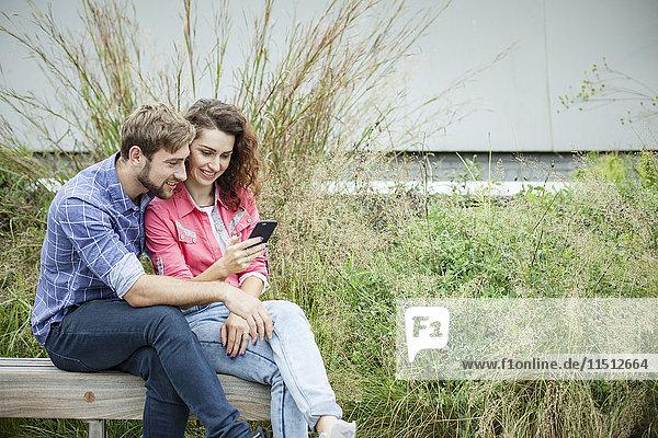 Paar sitzt zusammen auf der Parkbank und schaut auf das Smartphone.
