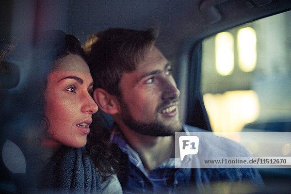 Paar schaut nachts aus dem Autofenster