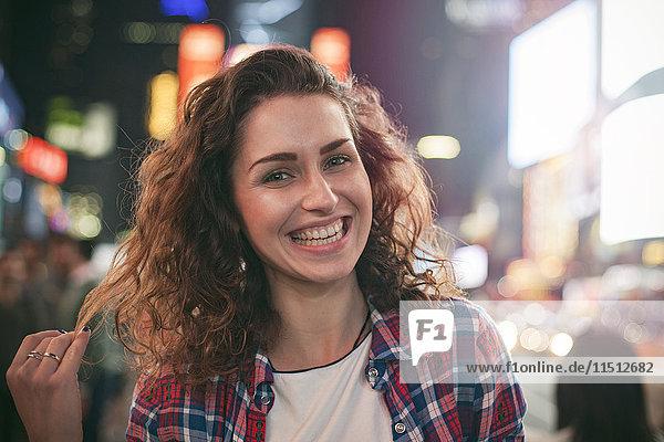 Junge Frau stehend in der beleuchteten Stadtstraße