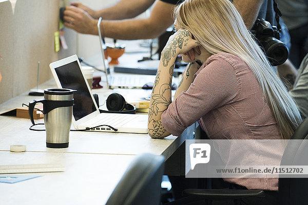 Frau konzentriert sich auf die Arbeit in gemeinsamen Büroräumen