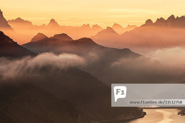Orange sky at dawn and mist on peaks of Dolomites and Fedaia Pass  Cima Belvedere  Val di Fassa  Trentino-Alto Adige  Italy  Europe
