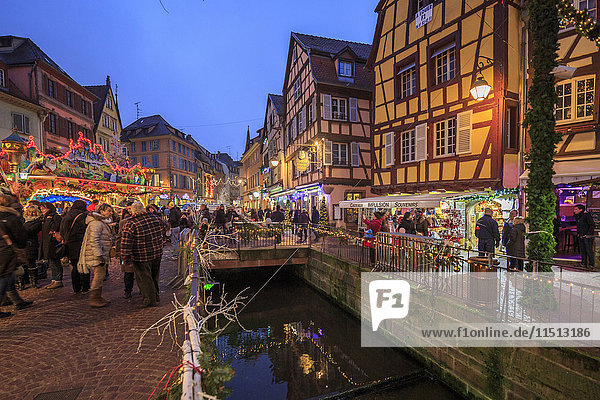 Tourists shopping at the Christmas Markets in the old medieval town of Colmar  Haut-Rhin department  Alsace  France  Europe