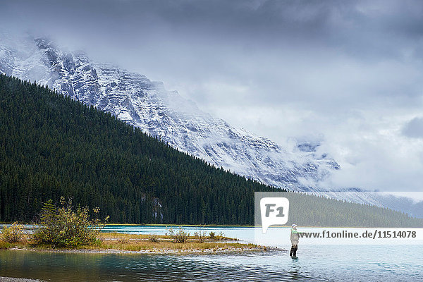 Man fly fishing in lake by snow capped mountains  Banff  Alberta  Canada