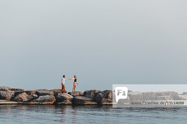 Distant view of couple holding hands on boulder wall  Lake Ontario  Toronto  Canada