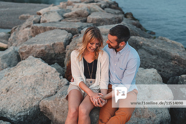 Romantic couple holding hands on boulder wall  Lake Ontario  Toronto  Canada