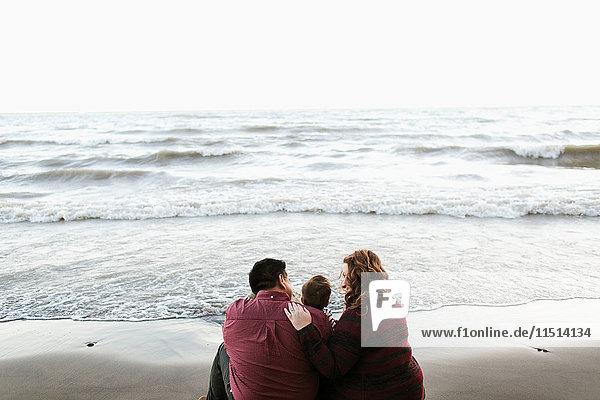 Rückansicht von Mutter und Vater am Strand sitzend