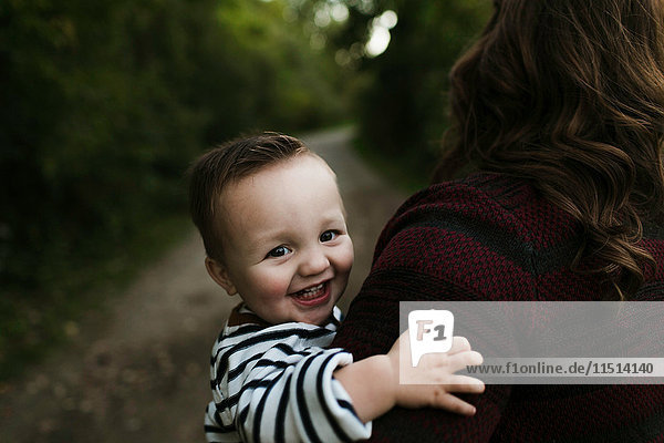 Baby boy in mother's arms looking at camera smiling