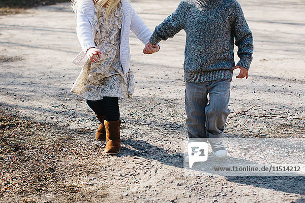 Siblings holding hands walking on gravel road