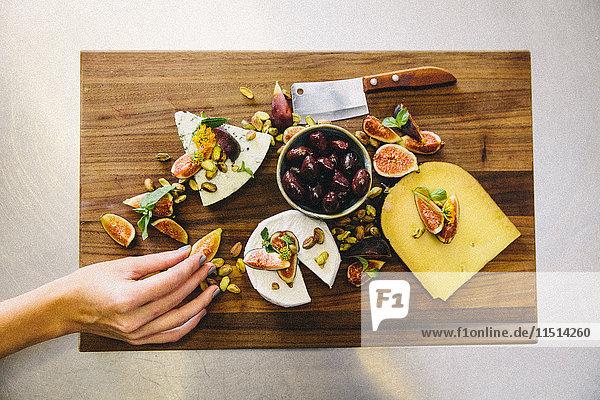 Käseplatte mit Feigen  Oliven  Pistazien  Beil auf Holzschneidebrett