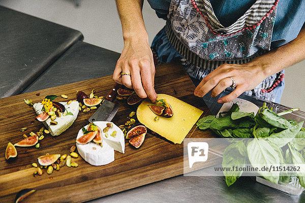 Frau bereitet eine Käseplatte mit Feigen  Nüssen  Pistazien und Basilikum auf einem hölzernen Schneidebrett zu