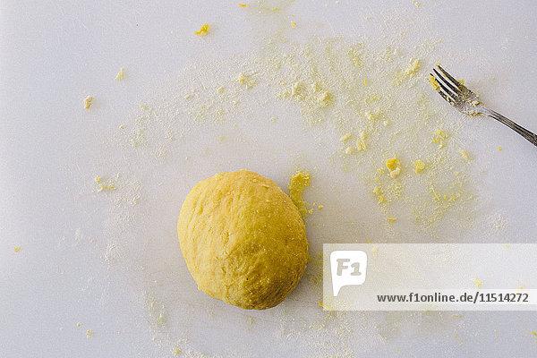 Pasta dough  fork on white chopping board