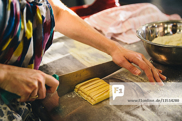 Woman cutting pasta dough with knife