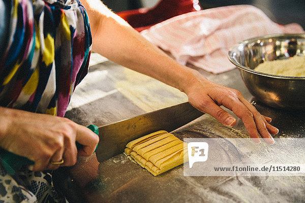 Frau schneidet Nudelteig mit Messer