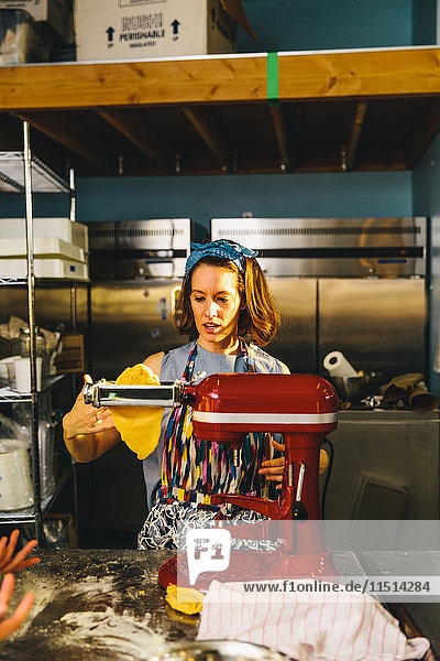 Woman flattening dough with pasta maker
