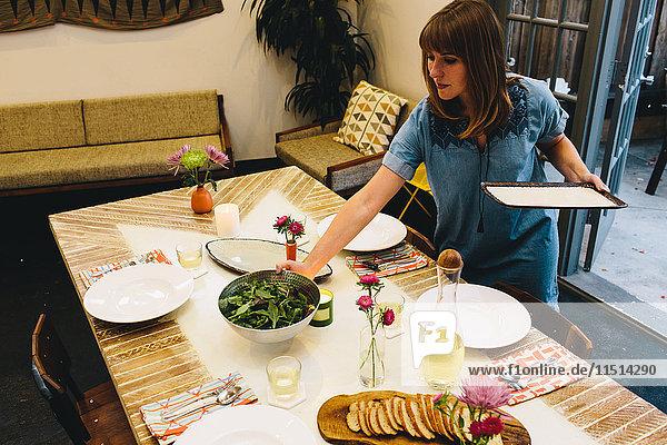 Frau stellt Geschirr auf den Esstisch