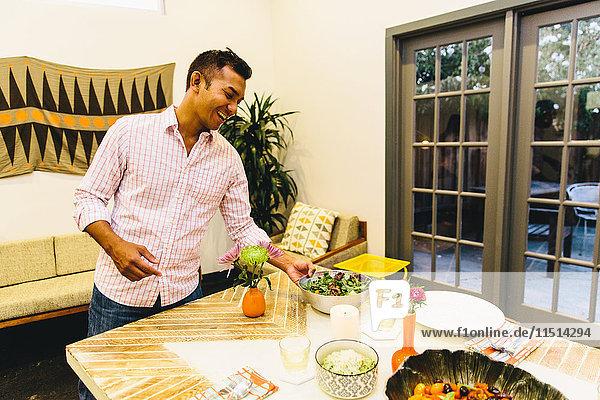 Mann stellt Geschirr auf den Esstisch