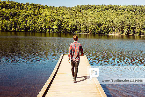 Man walking along wooden pier on lake  rear view