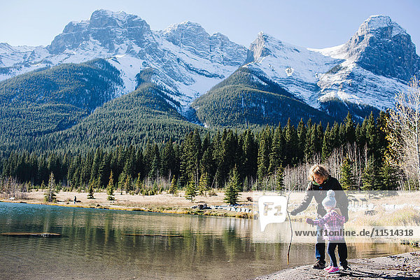 Grandmother and granddaughter beside river  Three Sisters  Rocky Mountains  Canmore  Alberta  Canada