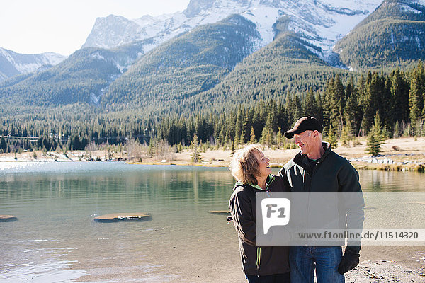 Senior couple standing beside river  Three Sisters  Rocky Mountains  Canmore  Alberta  Canada