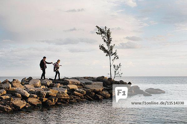 Young couple walking on rocks beside sea