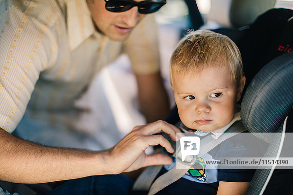Father securing young son in car seat