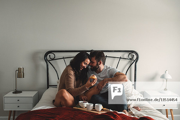 Romantic couple eating breakfast in bed