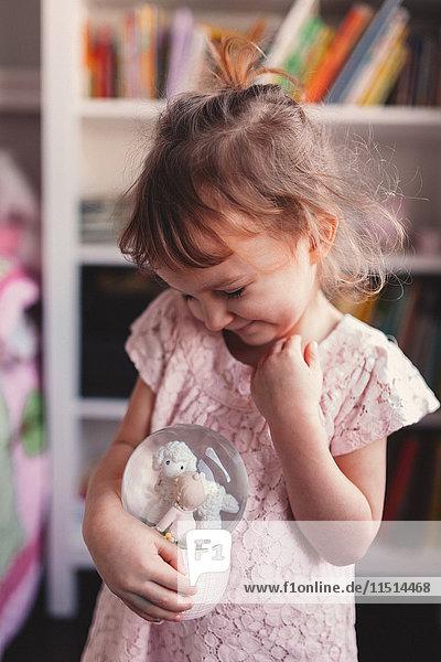 Girl in playroom holding lamb snow globe