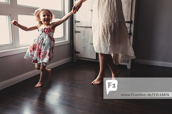 Süßes Mädchen läuft barfuß im Haus mit der Mutter Süßes Mädchen läuft barfuß im Haus mit der Mutter