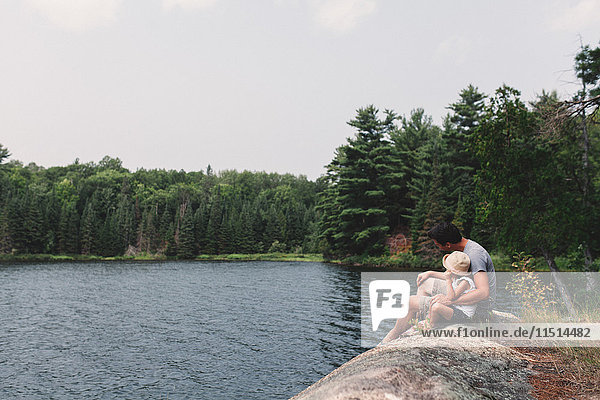 Young man and daughter sitting on rock at the edge of a lake
