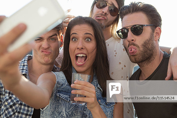 Junge erwachsene Freunde ziehen auf Dachterrassen-Party Gesichter für Selfie