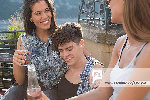 Drei erwachsene Freunde entspannen sich bei einer Dachterrassenparty  Budapest  Ungarn