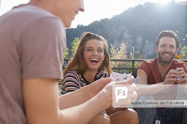 Erwachsene Freunde haben Spaß beim Kartenspielen auf der Dachterrassenparty