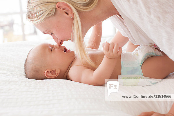 Mittlere erwachsene Frau Nase an Nase mit auf dem Bett liegendem kleinen Sohn