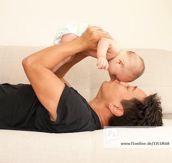 Reifer Mann liegt auf Bett und hält Baby-Sohn von Angesicht zu Angesicht