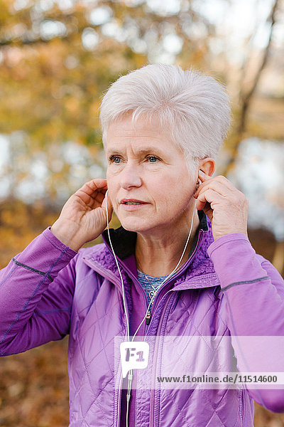 Ältere Frau in ländlicher Umgebung  die Kopfhörer trägt