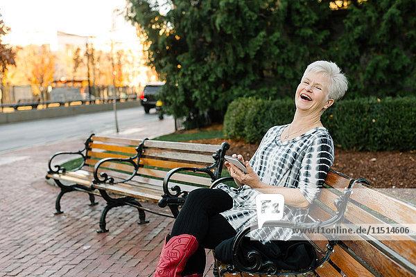 Porträt einer älteren Frau  im Freien  auf Bank sitzend  Smartphone haltend  lachend