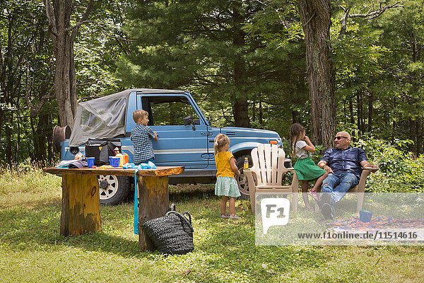Father and children sitting in woods beside off road vehicle