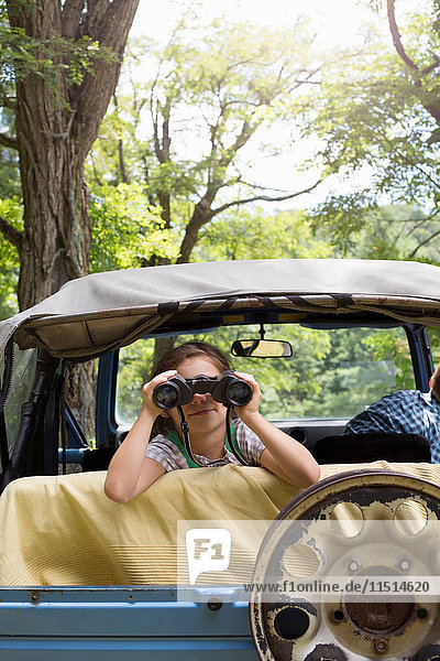 Young girl looking out of off road vehicle  using binoculars