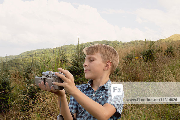 Young boy outdoors  looking at video camera