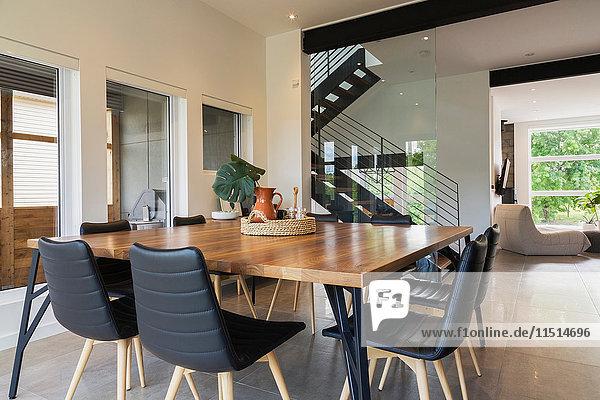 Esstisch aus amerikanischem Nussbaumholz und schwarze Lederstühle mit Eschenholzbeinen im Esszimmer in einem modernen Würfelhaus  Quebec  Kanada